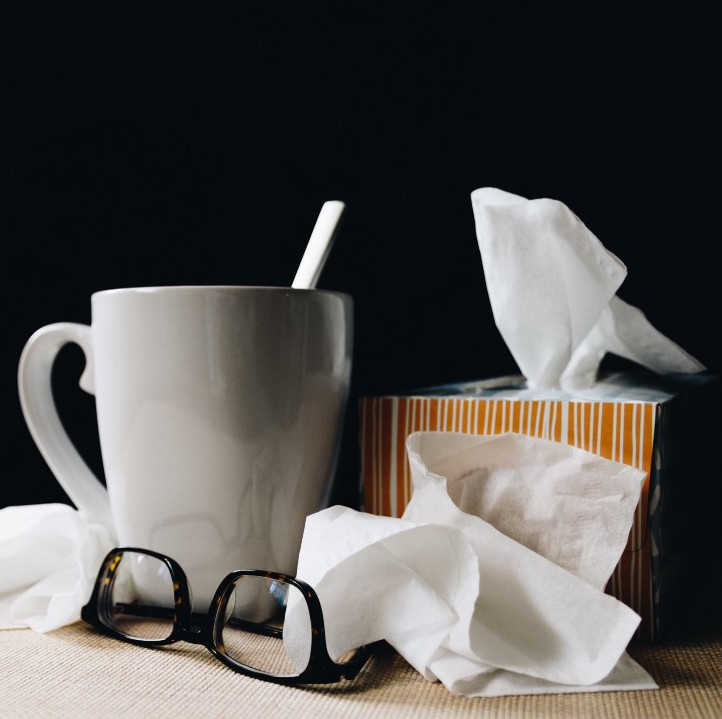 A white mug, pair of black eyeglasses and a box of tissues on a table