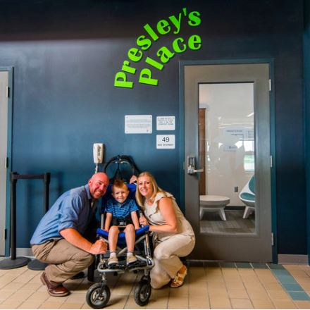 Jason Rudge, his wife, Sharon, and their son, Presley pose in front of the sensory room named for Presley at the Pittsburgh Airport.