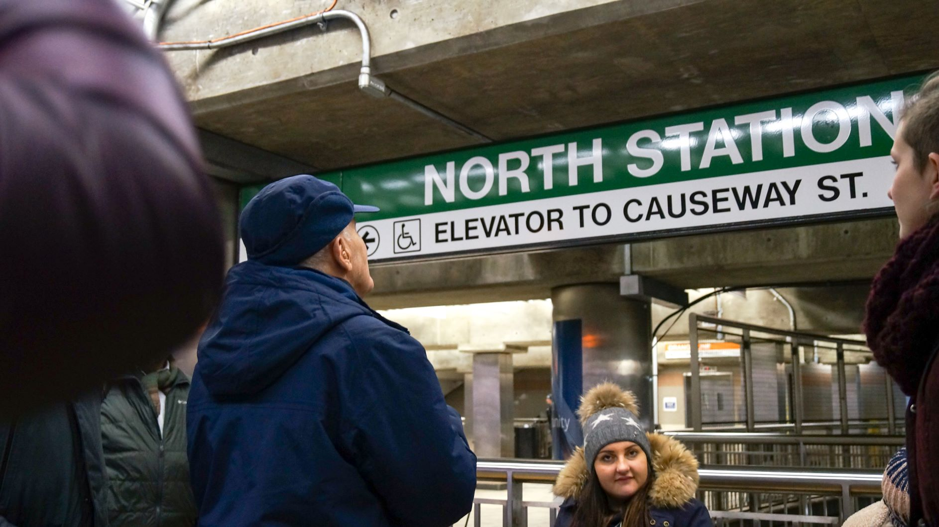 User/expert looks on at signage in North Station