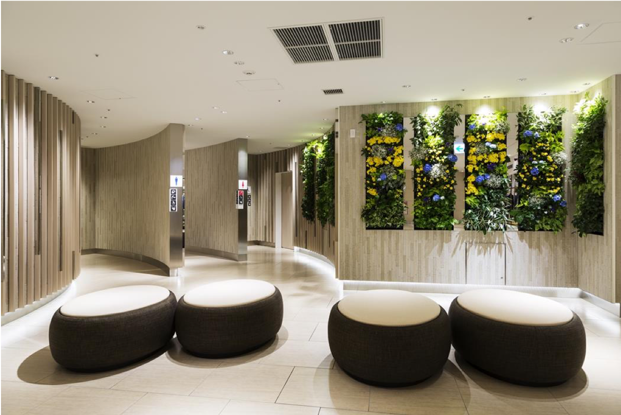 A public toilet with ambient lighting and seating provided in the common area. Vertical plants line the walls.
