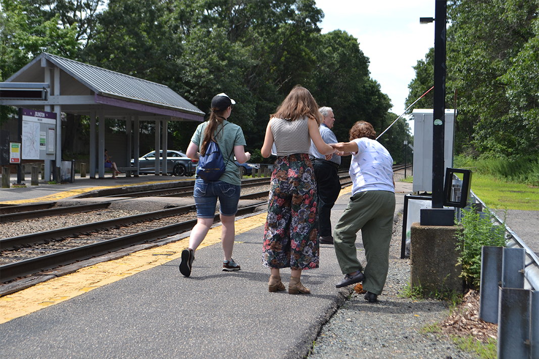 At MBTA train station, User/Expert being supported by IHCD intern to regain balance after she tripped off the path