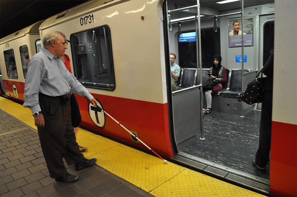 Vision impaired User/Expert trying to use his cane to locate the train door