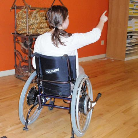 Woman in a wheelchair pointing